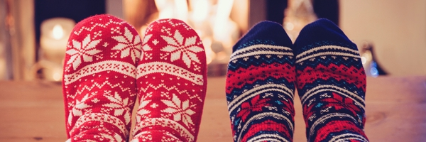 two people with holiday socks on in front of a fireplace
