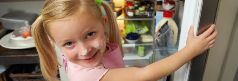 Little girl looking in fridge