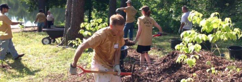 Employee volunteers help clean up a park.