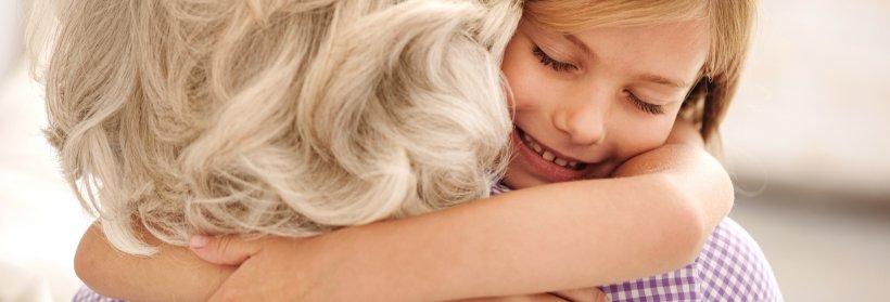 Young girl hugging grandmother.