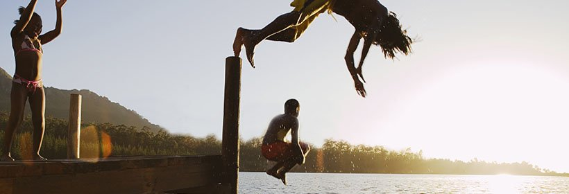 children jumping from a dock into a lake