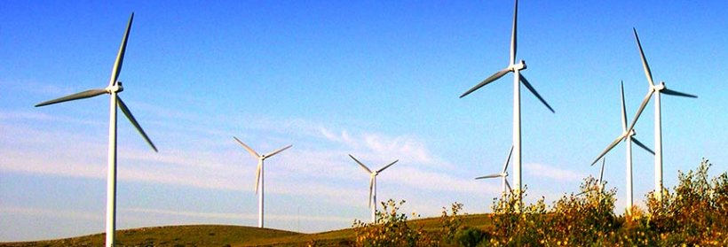 Field of three wind turbines with blue sky in background