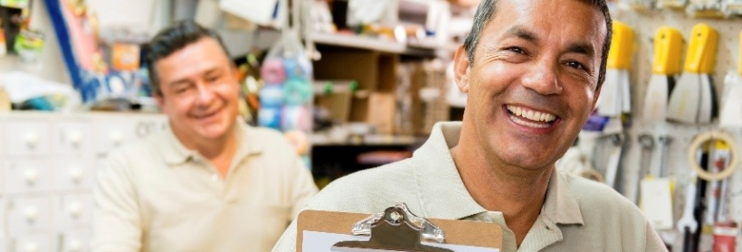 Business owner smiling and holding a clipboard